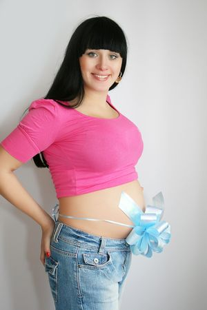 Pregnant Mother expecting a boy with blue ribbon around her stomach photo