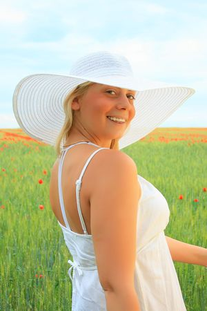 portrait of an attractive girl on a field with  wheat and poppies photo