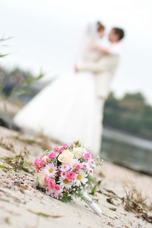 Brides bouquet . Kissing couple on the background.
