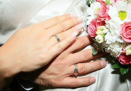 The bride and grooms hands together near wedding bouquet