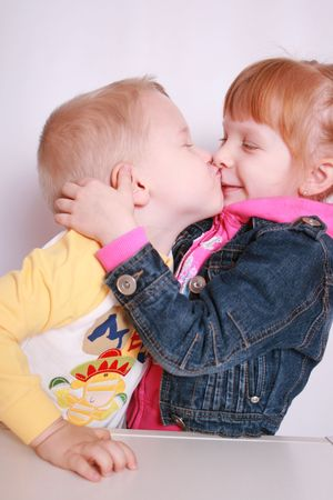 amused: Two small children in dressing gownes kiss, the boy with the girl