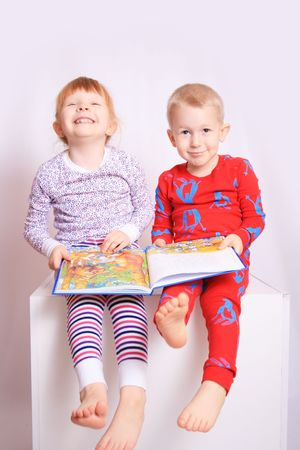familial affection: Happy children reading a book