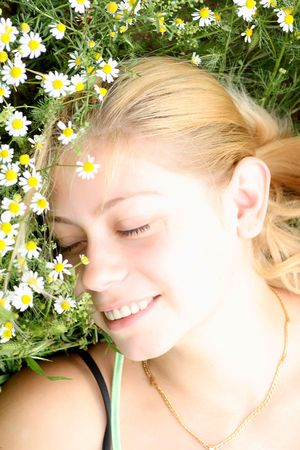 Woman lie on green grass with camomile flower Stock Photo - 6551308