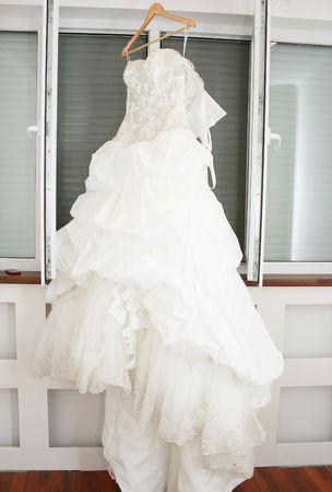 Beautiful white wedding dress hanging in a window. photo