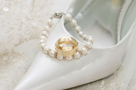 Wedding sandals and weddings  rings decoration over bridal veil photo