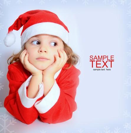 ni�os pensando: Retrato de una ni�a peque�a en el sombrero de Santa