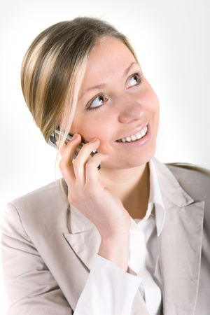 blonde business woman in beige suit jacket talking on cell phone photo
