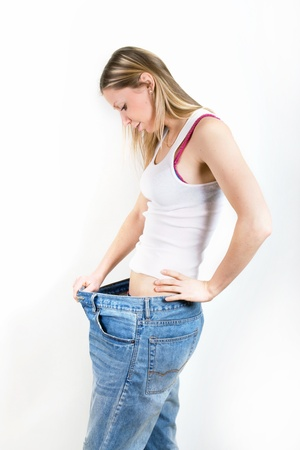 Happy young woman in old jeans pant after losing weight