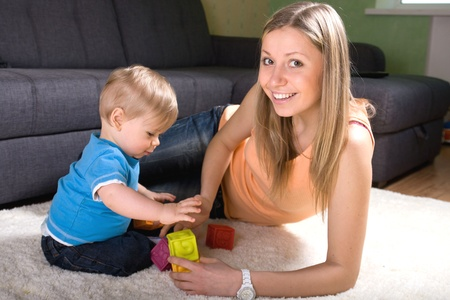 Young mother playing with baby boy ( 1 year old ) at home. Stock Photo