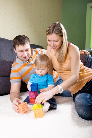 Family with baby boy sitting on floor at home and playing together. Stock Photo