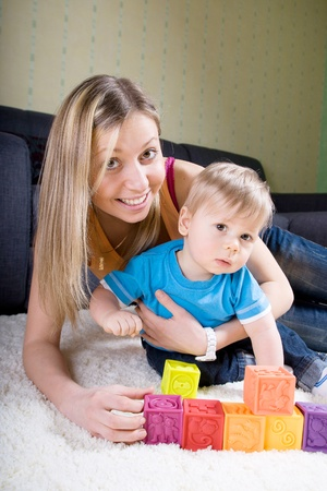 Young mother playing with baby boy ( 1 year old ) at home.