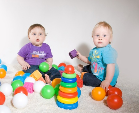interested baby: One year old babies  enjoy playing with toys. Studio Shot Stock Photo