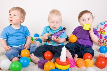 Un año viejos bebés disfrutan jugando con juguetes. Studio Shot