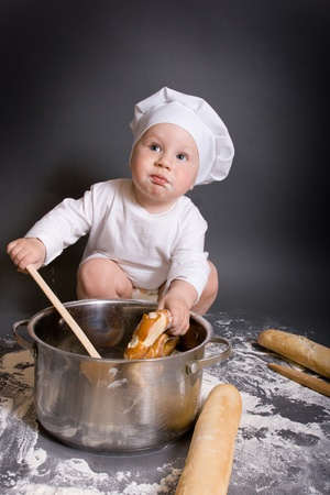 Little boy cook with kitchen accessories and hat photo