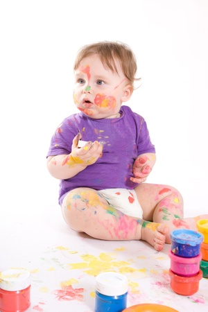 messy paint: Beautiful happy little baby painting with colors isolated on white background