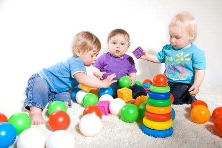 juguetes antiguos: Un a�o de edad los beb�s les gusta jugar con los juguetes. Foto de estudio Foto de archivo