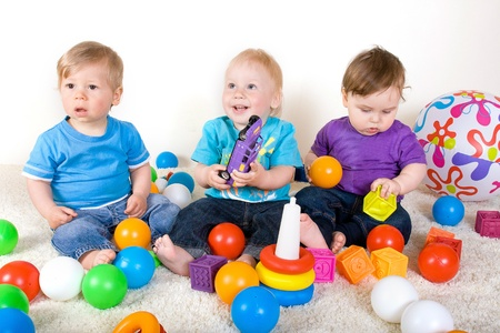 One year old babies  enjoy playing with toys. Studio Shot Stock Photo