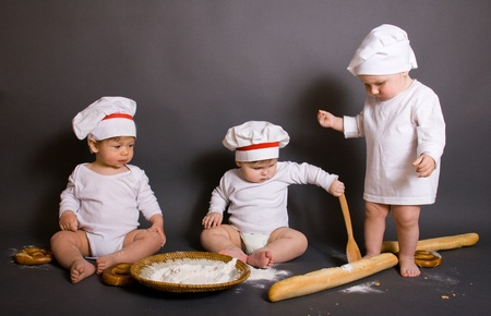three  Cute little boy in a suit of Food Boy with kitchen accessories. In the studio photo