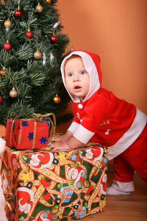 santa helper baby with christmas gifts over white Stock Photo