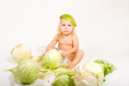baby girl sits in cabbage leaves photo