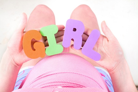 A pregnant woman is holding letter that spell out the word girl photo