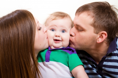vater und baby: Junge gl�ckliche Eltern k�ssen baby boy Lizenzfreie Bilder