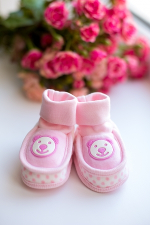 Baby girl shoes and pink roses on a table. new born girl shoes . photo