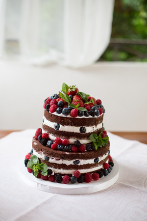 Delicious chocolate cake with cream and berries photo