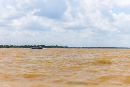 On the Mekong river at Vietnam. Crossing the Mekong river near the city of Saigon or Ho Chi Ming City. Water splashing under blue sky with white clouds. Brownish water of the huge river Zdjęcie Seryjne