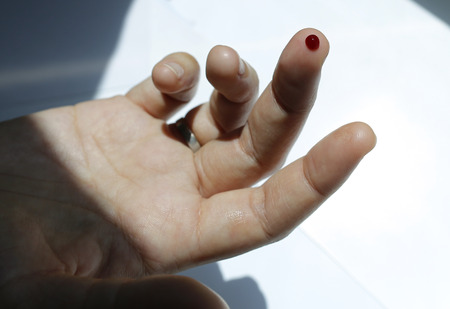 A finger with red blood drop
