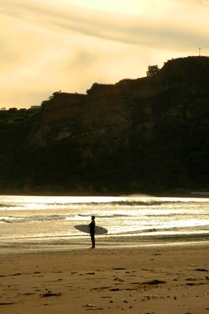 Surfer watching the sunset on a beach in Nicaragua photo