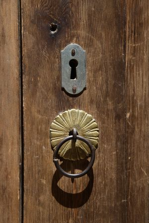 inlaid: An old wooden door with inlaid door-knocker and lock