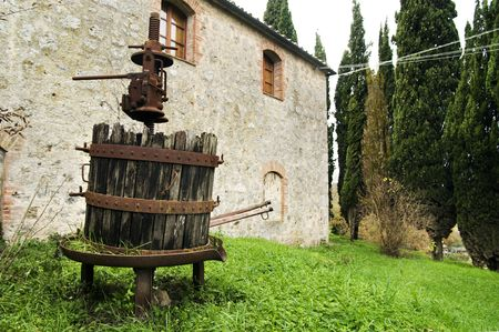 disuse: Old machinery with wood and rusted iron in front of a stone farm in Tuscany
