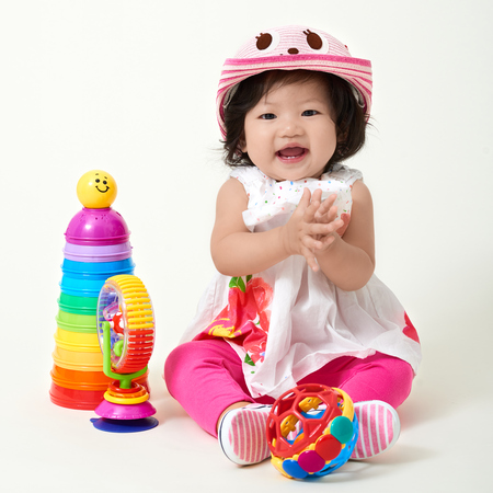Asian baby girl wearing colorful outfit playing with toys.