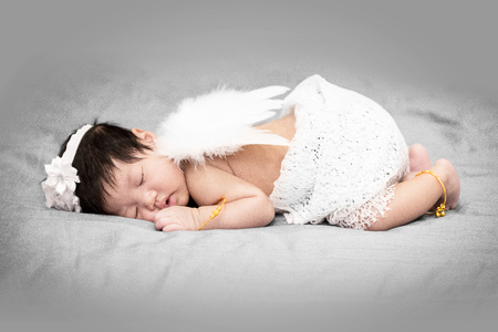 Sleeping Asian baby angel in peace. White outfit and wings. Stok Fotoğraf