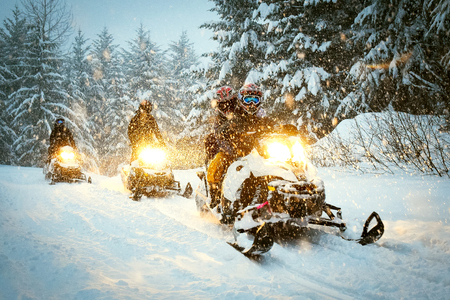 Snow mobile in blizzard through the woods and forest