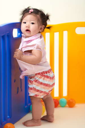 Asian Chinese baby girl playing with colorful balls fenced. Stock Photo