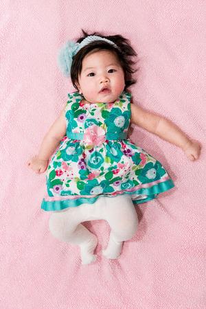 かわいい花柄のドレスとピンクの背景で女の赤ちゃん 写真素材