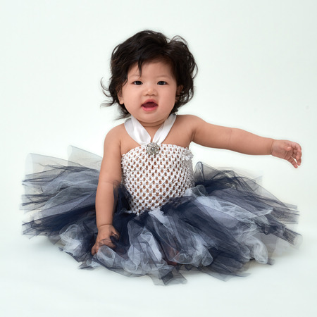 flare up: Cute Asian baby girl in flare dress sitting up. Stock Photo