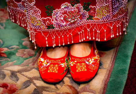Traditional red Chinese wedding shoes on the bride