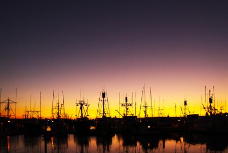 澄んだ空と反射でドッキング ボートの日没のシルエット