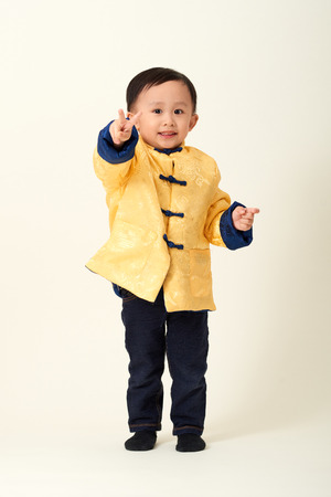 Chinese baby boy in traditional Chinese New Year outfit celebrating Lunar New Year Stock Photo
