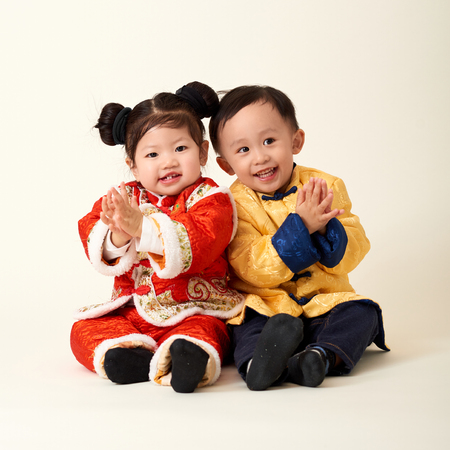 Chinese baby boy and girl in traditional Chinese New Year outfit celebrating Lunar New Year Stock Photo