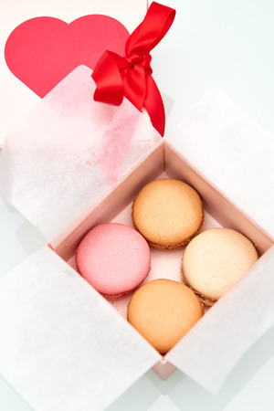 4 colorful macaroons wrapped in the Valentines Day themed pink box with red heart and bow on top of the box. Stock Photo
