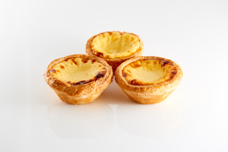 3 smakelijke Portugese Custard Taarten met reflectie geïsoleerd op een witte achtergrond