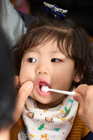Asian baby toddler girl is brushing her white teeth before going to sleep.