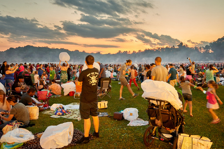 Crowd hanging out on the field for sunset in order to launch the lanterns on Lantern Festival in PA June 10th 2017.