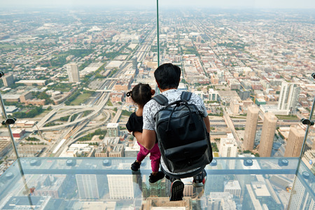 CHICAGO, IL - SEPTEMBER 2, 2017 : Father and daughter on the ledge at the Skydeck of the Willis Tower. The Skydeck is on 103rd floor of the Willis Tower, the eighth tallest building in the world. Editorial