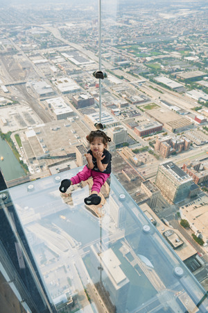CHICAGO, IL - SEPTEMBER 2, 2017 : Little girl is standing on the ledge at the Skydeck of the Willis Tower. The Skydeck is on 103rd floor of the Willis Tower, the eighth tallest building in the world. Editorial