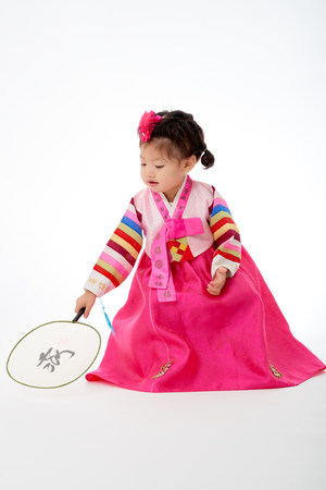 Smile Korean little girl wearing a Traditional Hanbok dress and holding a fan in white background. The characters on the dress means happiness and healthy. The character on the fan means happy. Standard-Bild